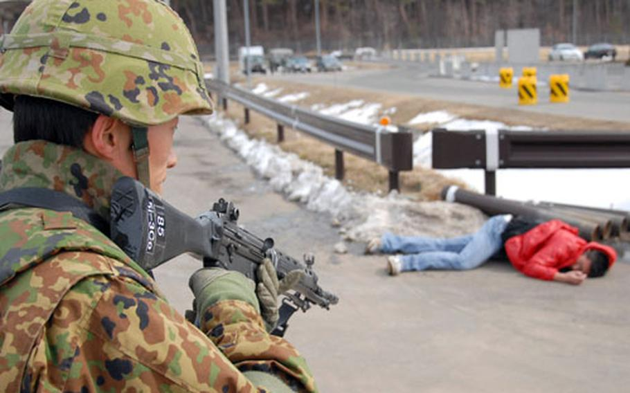 """A member of the Japan Ground Self-Defense Force 9th Division, 5th Infantry Regiment stands watch over the cornered """"terrorist."""""""