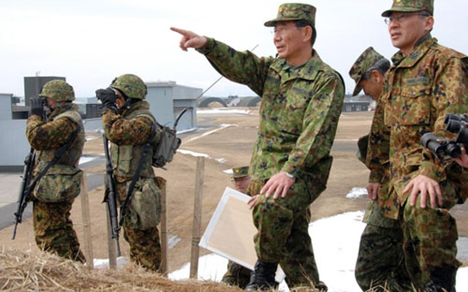 """Lt. Gen. Akiyo Mimoto, commander of the Japan Ground Self-Defense Force 9th Division, 5th Infantry Regiment, points out over Misawa Air Base, Japan, during the exercise. The 9th Division teamed with the Japan Air Self-Defense Force 3rd Air Wing and U.S. airmen of the 35th Security Forces Squadron for the annual """"Exercise Guard and Protect."""""""