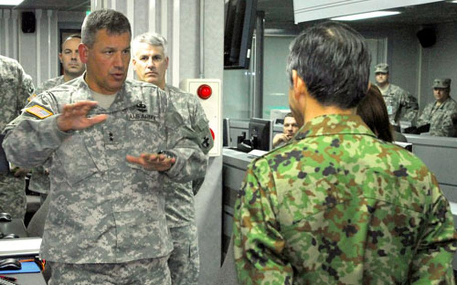 Maj. Gen. Raymond V. Mason, commander of the 8th Theater Sustainment Command, briefs Maj. Gen. Yoshikazu Watanabe, director of logistic for the Japanese Ground Self-Defense Force at the 8th TSC forward command post at Camp Zama on Wednesday.