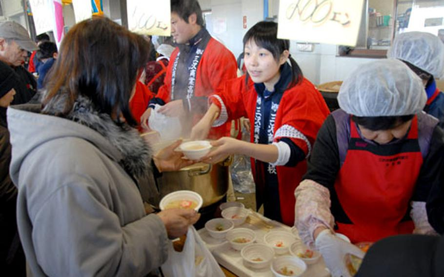 Workers hand out steaming bowls of hokki stew.