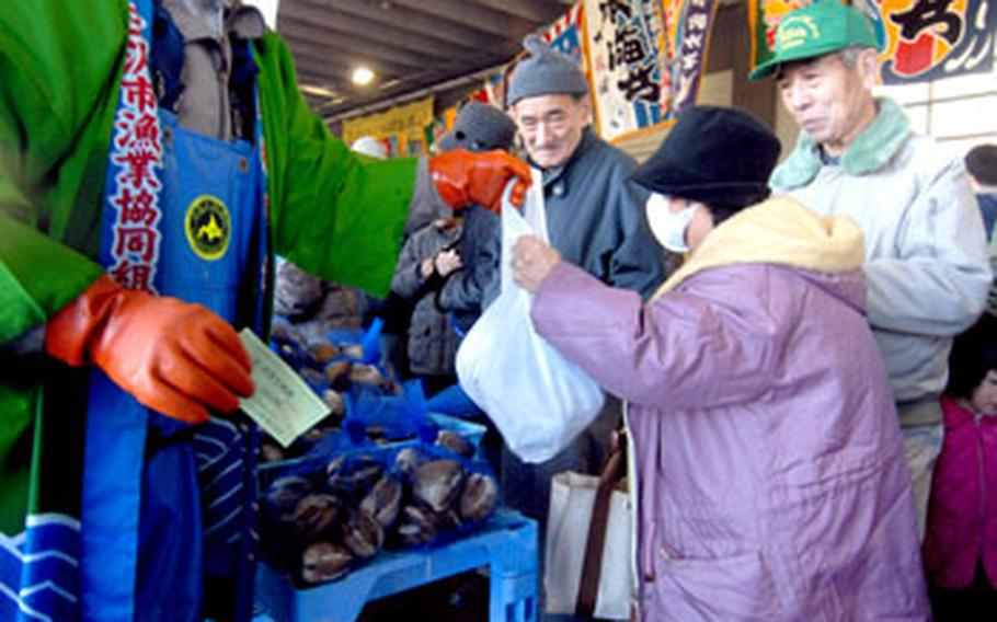 A worker grins as he hands a bag of surf clams to a shopper.