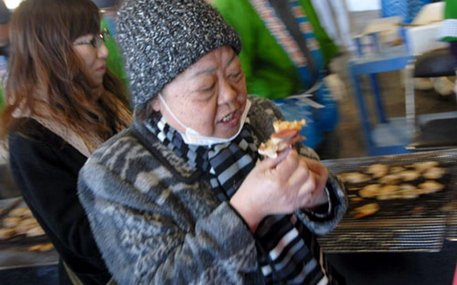 A Japanese woman gets ready to bite into freshly grilled hokki.