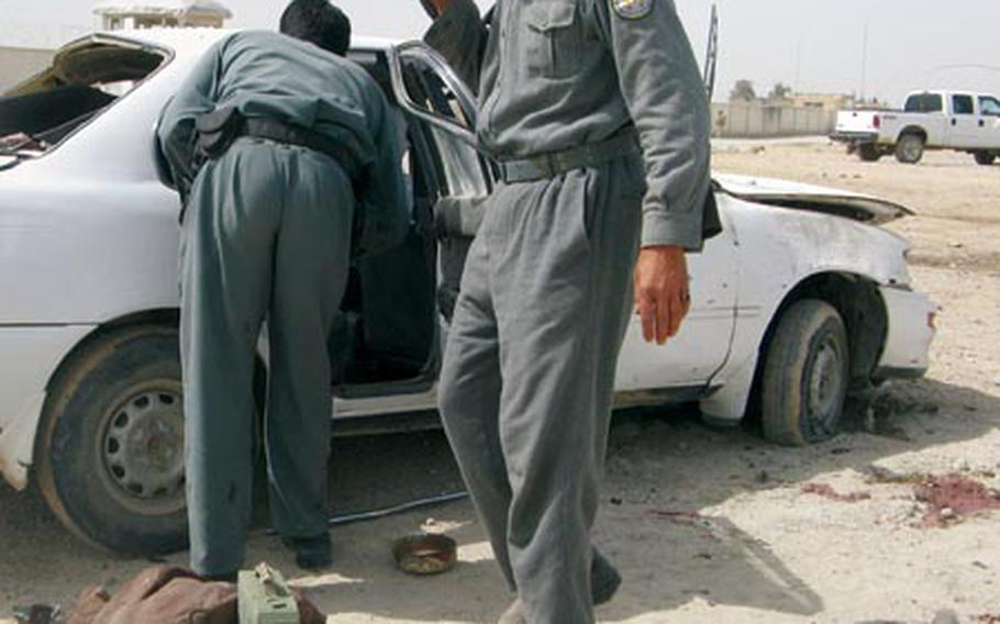 An Afghan police officer looks on the blood stains following a suicide attack in Lashkar Gah, the capital of Helmand province, south of Kabul, Afghanistan on Monday, March 16, 2009. The suicide bomber in a police uniform detonated explosives he was carrying inside a police headquarters on Monday, killing 11 people and wounding 29 others, the Interior Ministry said.