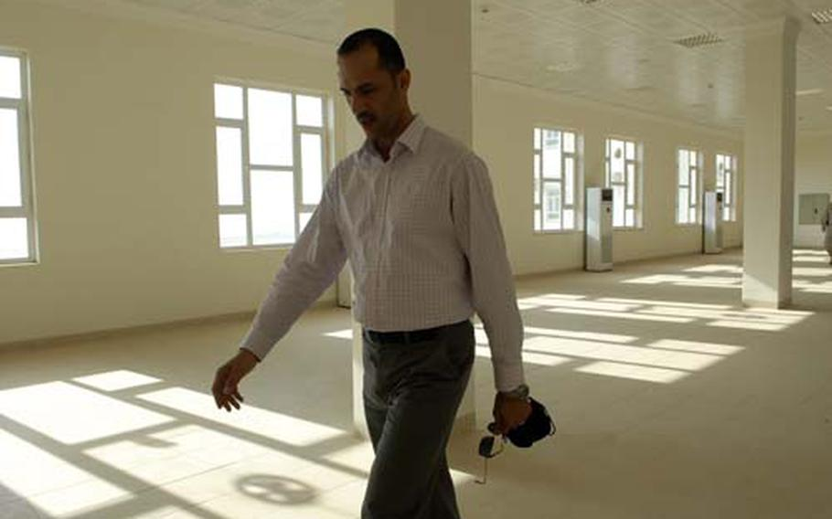 Hassan Hayder, an engineer working with the U.S. Army Corps of Engineers, walks the empty halls of Irbil's new police academy. The $15 million project sits empty because the Kurdistan Regional Government has not received the final $5 million in U.S. funds it expected to furnish the complex and hook up water and electricity.