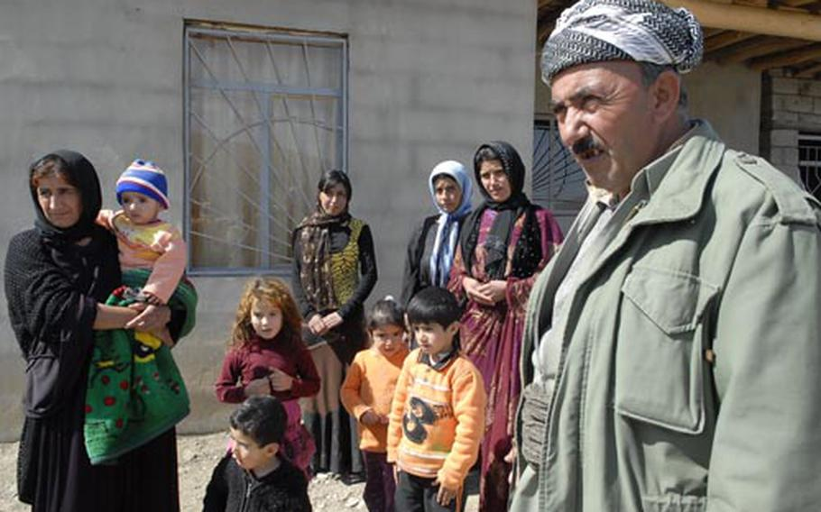 Othman Shekh Issa, foreground, stands with his family outside his ramshackle home in Soran, a city in the mountains of Irbil Province. Issa, like many Kurdish farmers, was chased from his home deep in the Candil mountains by Turkish bombing and Iranian artillery aimed at militants from the Kurdistan Worker's Party (PKK), labeled a terrorist group by the United States. Issa, his wife, and eleven children now live in the cramped three-room home.