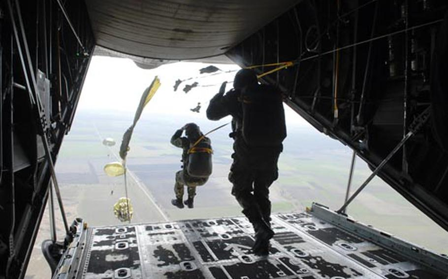Bulgarian paratroopers jump from the open rear hatch of a C-130E, hands holding helmets and legs apart, during Operation Thracian Spring 2009 last week in Bulgaria.