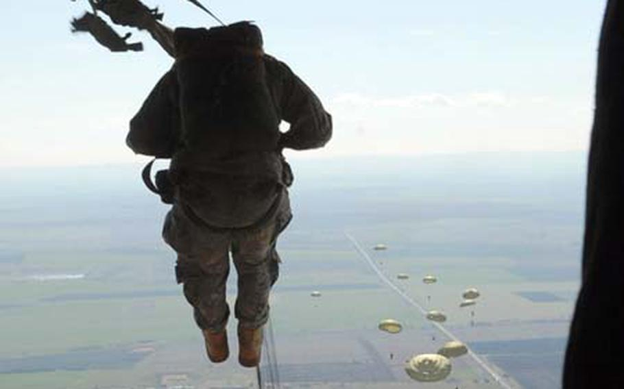 A U.S. paratrooper jumps from a C-130E aircraft with arms tightly in front of his body and feet together and forward during a static-line jump with Bulgarian paratroopers.