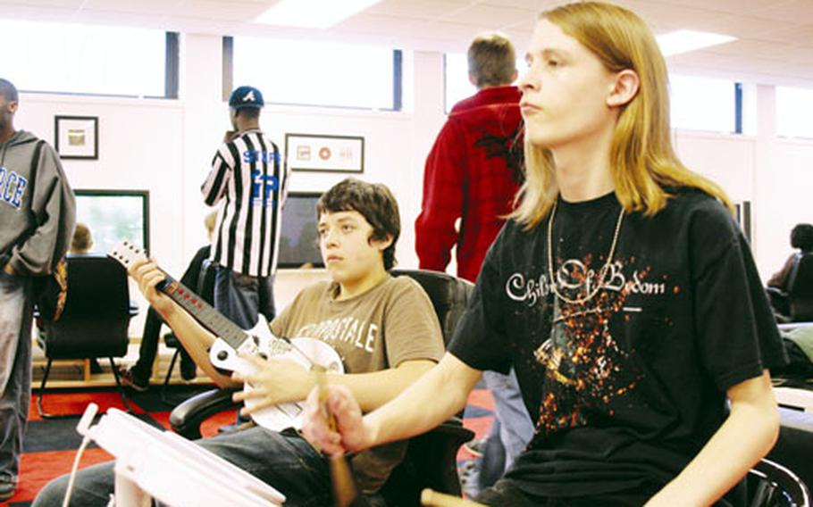 """Thomas Cleary, right, 18, and Brandon Fasnacht, 15, both students at Lakenheath High, play the video game """"Rock Band"""" at the newly opened Page Community Center at RAF Lakenheath."""