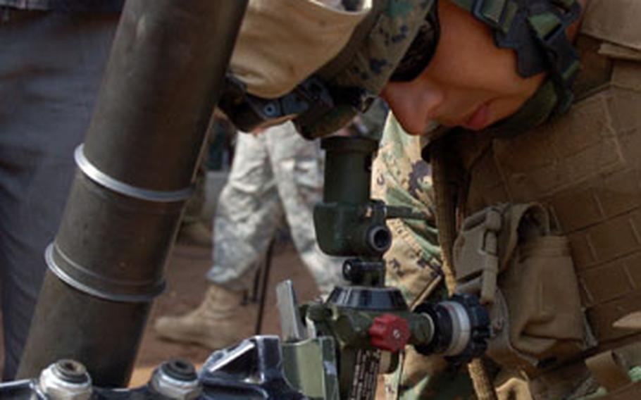 Cpl. Rick Velasquez checks the site on a 60-mm mortar Tuesday during the annual Key Resolve/Foal Eagle Exercise at Rodriguez Range in South Korea.