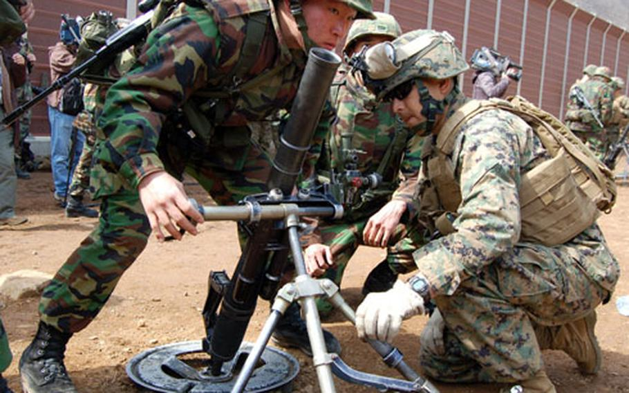 Cpl. Rick Velasquez, right, L Company, 3rd Battalion, 5th Marine Regiment, and Lance Cpl. Kim Ju-Kyoung, 5th Company, 2nd Battalion, 8th Marine Regiment train, on a 60 mm mortar on Tuesday at Rodriguez Range, South Korea, during the annual Key Resolve/Foal Eagle Exercise.