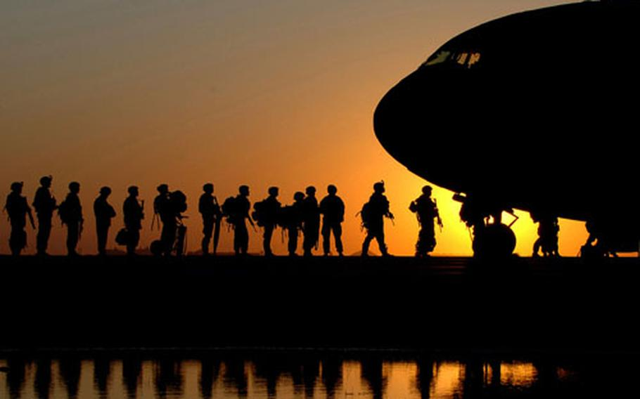 The sun sets behind a C-17 Globemaster III as Soldiers wait in line to board the aircraft taking them back to the United States Nov. 17 at Joint Base Balad, Iraq.