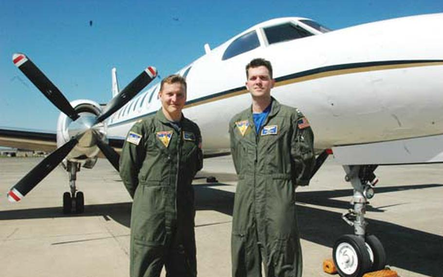 Lt. Cmdr. Bill Roark, left, and Lt. Danny Abad, both Navy pilots, stand in front of one of two C-26 Metroliner aircraft stationed at Naval Air Station Sigonella, Sicily. The aircraft are used for rapid transport of passengers and cargo through the European theater. Two other aircraft are based in Naples, Italy.