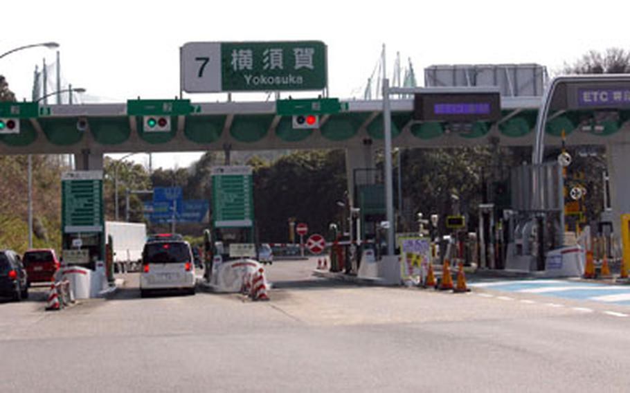 Cars line up to pay tolls at the Yokosuka interchange on the Yokohama-Yokosuka Expressway on Thursday. Tolls on expressways in Japan will be getting cheaper March 28, but only for drivers using Electronic Toll Collection.