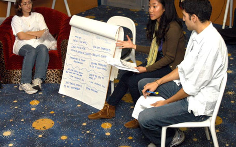 Monique Rose, center, and Andrew Jajja, right, talk with high school students at the Yokosuka Astrolounge teen center on Thursday as part of their Voice, Identify and Produce program. Love, 20, was raised at Yokosuka Naval Base until she left for college at New York University.