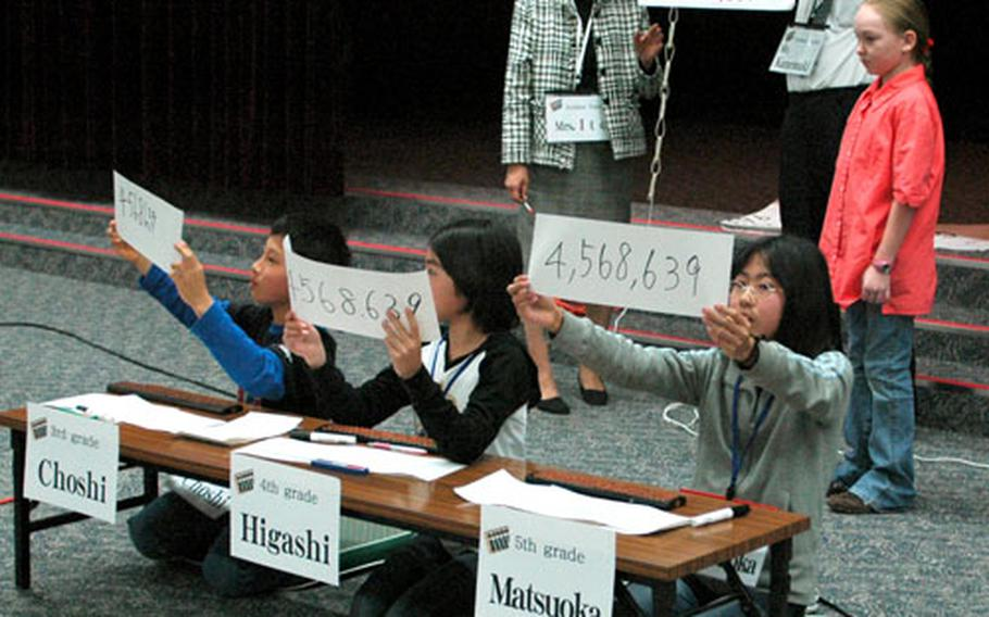 Six students from nearby Japanese soroban schools display their answers to students and faculty at Joan K. Mendel Elementary School, Yokota Air Base, Japan, during a soroban demonstration Friday. Soroban, a Japanese style of abacus, allows a skilled user to perform large calculations in only a few seconds.