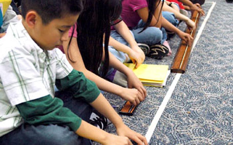 Students at Joan K. Mendel Elementary School at Yokota Air Base, Japan, use sorobans, or Japanese abacuses, to solve math problems during a demonstration Friday.