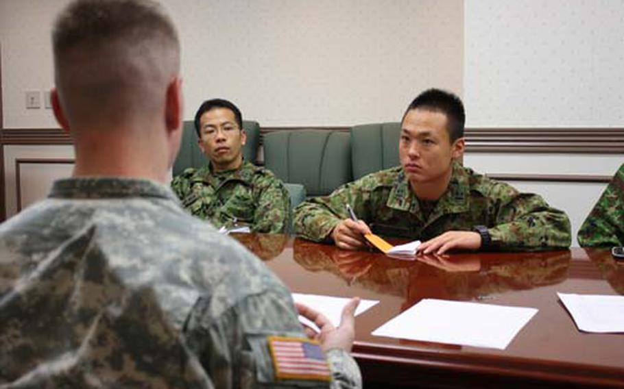 1st Lt. Masahito Fukayama of the Japan Ground Self-Defense Force listens intently as he receives instruction from a Camp Zama sponsor in the Co-op program. The program helps Japanese soldiers build leadership and English skills.