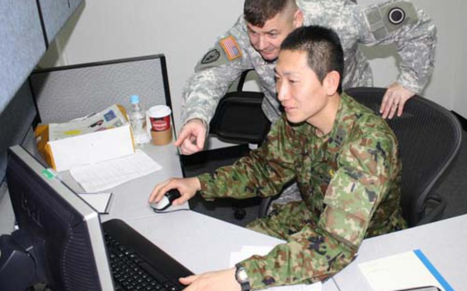 Maj. Ed Miiller gives computer advice to 1st Lt. Masashi Higashiyama of the Japan Ground Self-Defense Force. Miiller recently finished his fifth go around as a sponsor in Camp Zama's Co-op program.