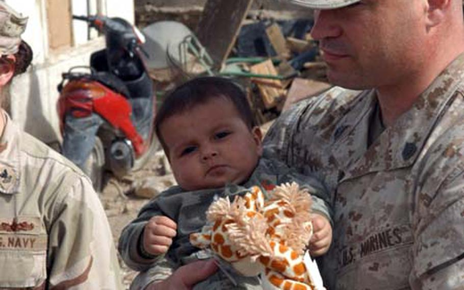 Marine Corps Gunnery Sgt. Carson Jeffers, of the Multi-national Security Transition Team-Iraq, holds a baby during a visit to an impoverished family that has lived in the green zone since 2004. U.S. troops have taken the family under their wing, providing them with water, toys and other items.