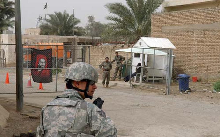 Air Force Staff Sgt. Luis Alcantar, a Green Zone police officer, patrols outside an Iraqi checkpoint. Since the U.S.-Iraq Security Agreement went into effect Jan. 1, more areas of the green zone have come exclusively under Iraqi control and are no-go zones for U.S. troops. The Iraqis here are guarding the entrance to a block of apartments.