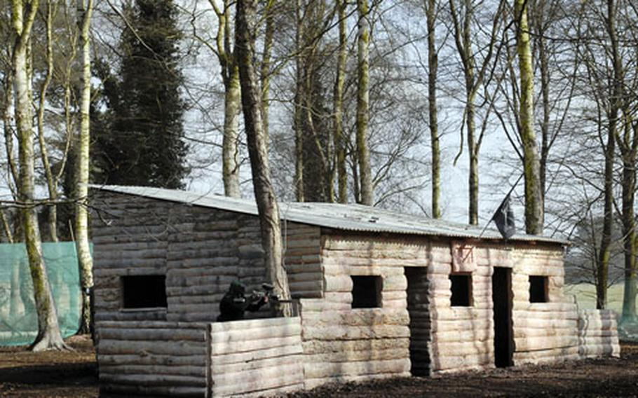 A paintballer protects the lodge in a timed game in which the attacking team has about 10 minutes to take the lodge by advancing and shooting everyone inside.
