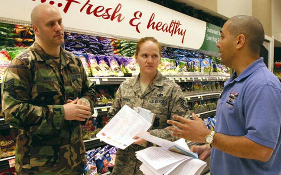 """Staff Sgt. Michael White and Tech. Sgt. Stacie Conrey get healthy eating tips while touring the commissary at RAF Lakenheath with Tech. Sgt. Michael DeCarmo from the base's Health and Wellness Center. """"You gotta have a game plan,"""" DeCarmo said."""