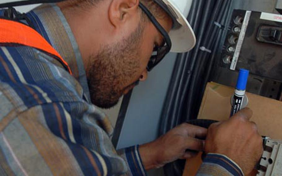 Mohammad Addi works on an electrical box on March 15 at Camp Lemonier, Djibouti. Electrical projects that now allow the camp to provide its own power were an essential step for the camp's growth toward being a key installation.