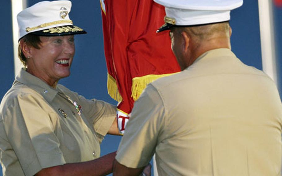 Then-Brig. Gen. Mary Ann Krusa-Dossin receives the ceremonial colors from Brig. Gen. Joseph V. Medina during a change-of-command ceremony at Camp Butler on Sept. 6, 2006.