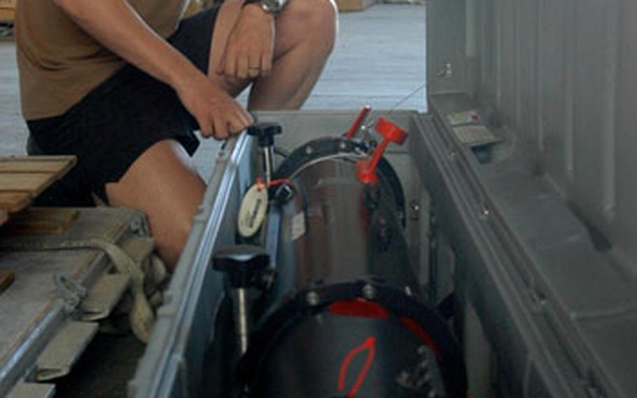 Petty Officer 1st Class Michael Beauregard, a sonar technician stationed in Sigonella, Sicily, crouches next to side-scan sonar unmanned underwater vehicle. He and two other sailors will take three units to Uganda.