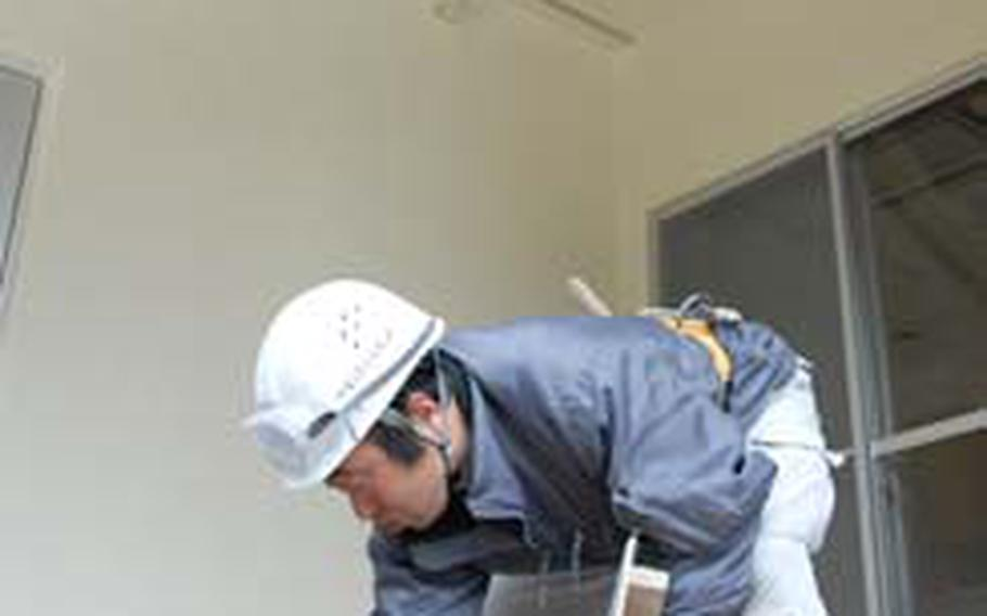 A Japanese worker with Obayashi Construction places outdoor tile in a housing unit on Misawa Air Base, Japan, on Thursday. Officials say the first phase of the multimillion-dollar project will be complete in late May, opening 281 renovated housing units to the base community.