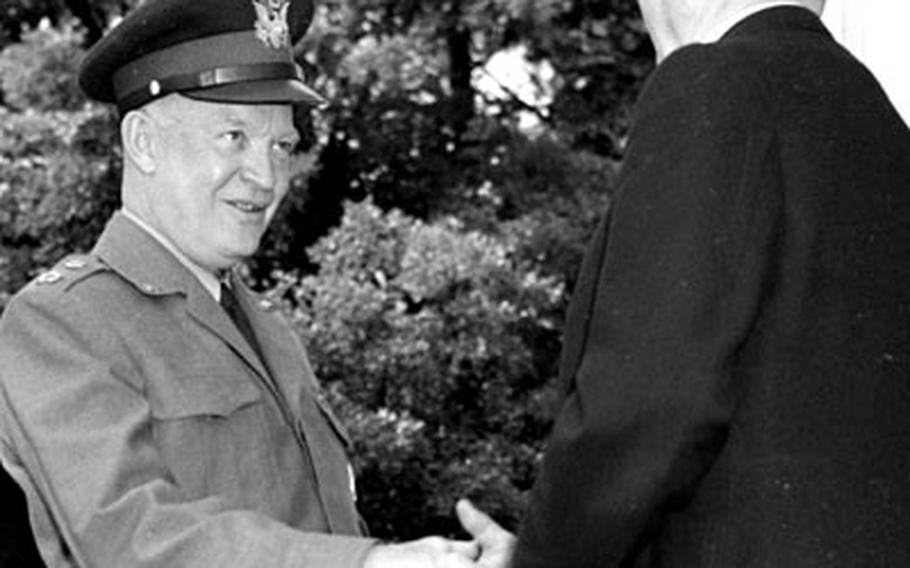 Chancellor Adenauer greets Gen. Eisenhower.