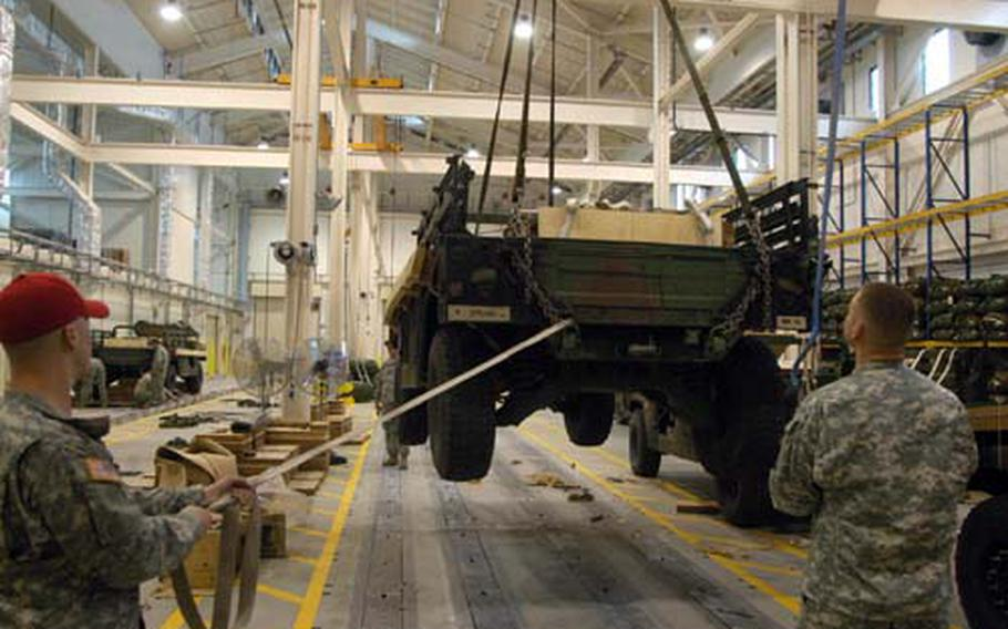 Spc. Brett Jones, left, and Sgt. Joshua Gardner use a crane to lift a Humvee inside the massive heavy drop facility at Aviano Air Base, Italy. The facility, used for the first time this weekend, is the largest of its kind for the U.S. military in Europe and is designed as a workplace for riggers to prepare heavy equipment for aerial drops.