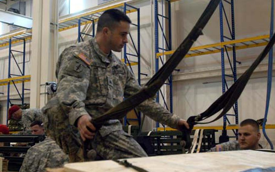 Sgt. Heath Barber, the shop foreman at the heavy drop facility at Aviano Air Base, Italy, prepares to attach cables from an overhead crane to a Humvee.