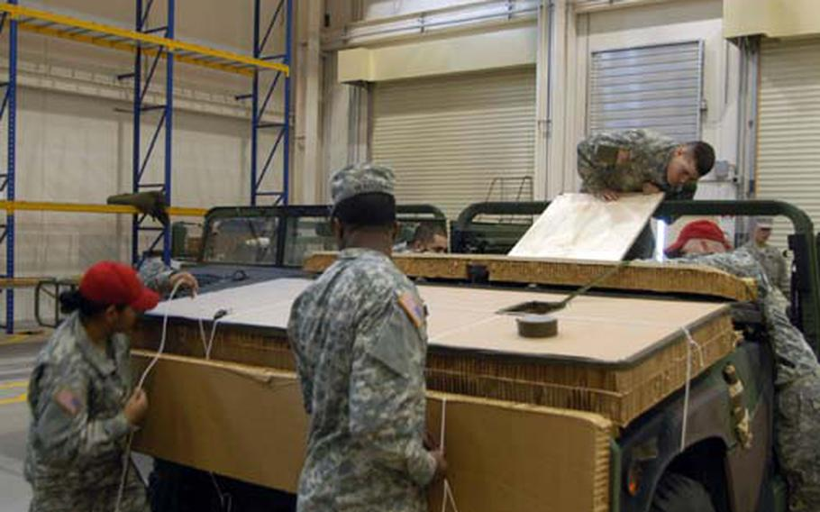 Soldiers assigned to the 2nd Battalion, 503rd Infantry Regiment and 173rd Base Support Battalion cover a Humvee with protective material while preparing it to be dropped from an airplane at the heavy drop facility.