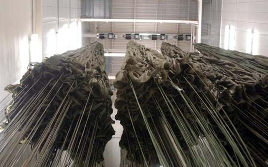 A handful of G-11 parachutes, which weigh about 250 pounds and are capable of supporting about 5,000 pounds in the air, hang in the drying tower at the heavy drop facility at Aviano Air Base, Italy. Parachutes that get wet need to be dried before they're used again.