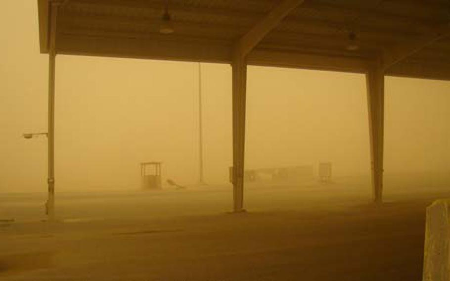 A sand storm blankets Khabari Alawazem Crossing, also known as K-Crossing, along the Kuwait-Iraq border. K-Crossing is a Kuwaiti military installation where all military-related traffic must pass on the way to and from Iraq.