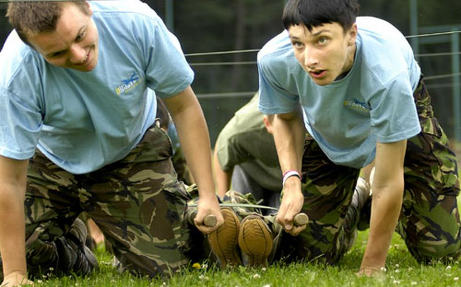 Alex Gliddon, left, and James Bennett, both air cadets from the United Kingdom, drag another cadet on a litter through an obstacle course Wednesday at Kapaun Air Station.