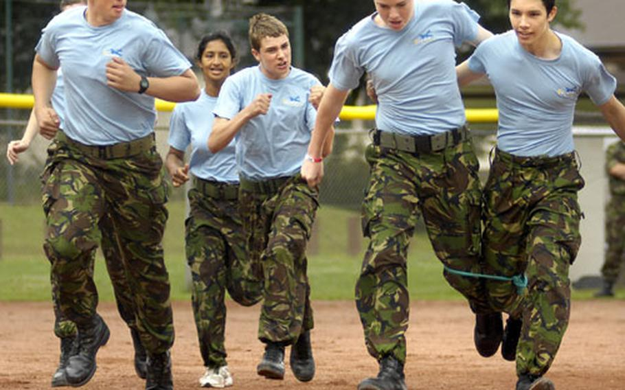Joules Roberts, right, and Tony Ledger, both air cadets from the United Kingdom, stride through a three-legged race with the moral support of their team Wednesday at Kapaun Air Station, Germany.