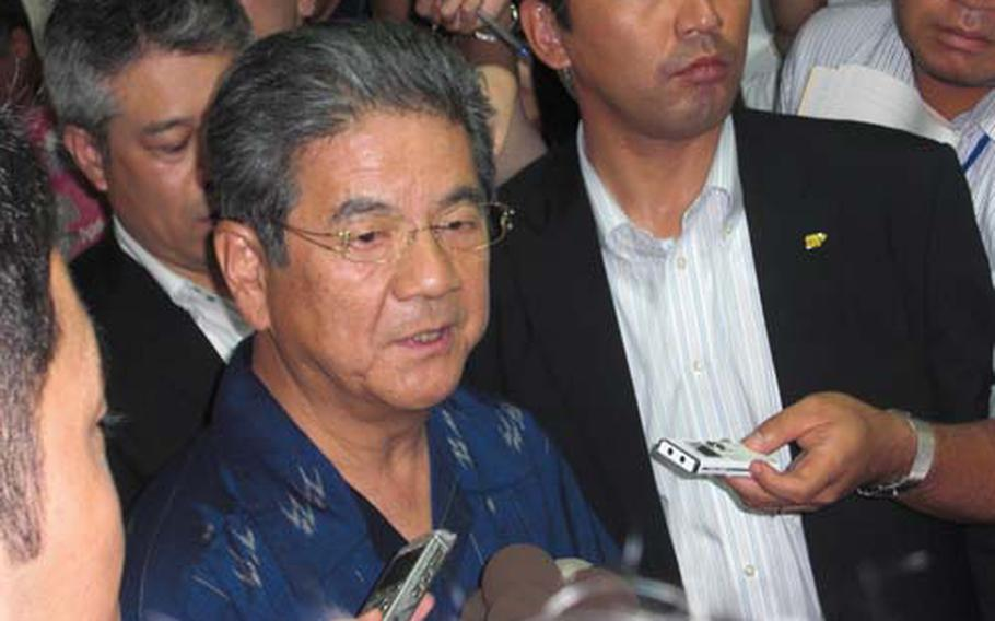 Japan Defense Minister Toshimi Kitazawa is surrounded by reporters Friday following his meeting with Okinawa Gov. Hirokazu Nakaima in Naha. Kitazawa is on a fact-finding visit to gather input on plans to move U.S. air operations from Marine Corps Air Station Futenma.