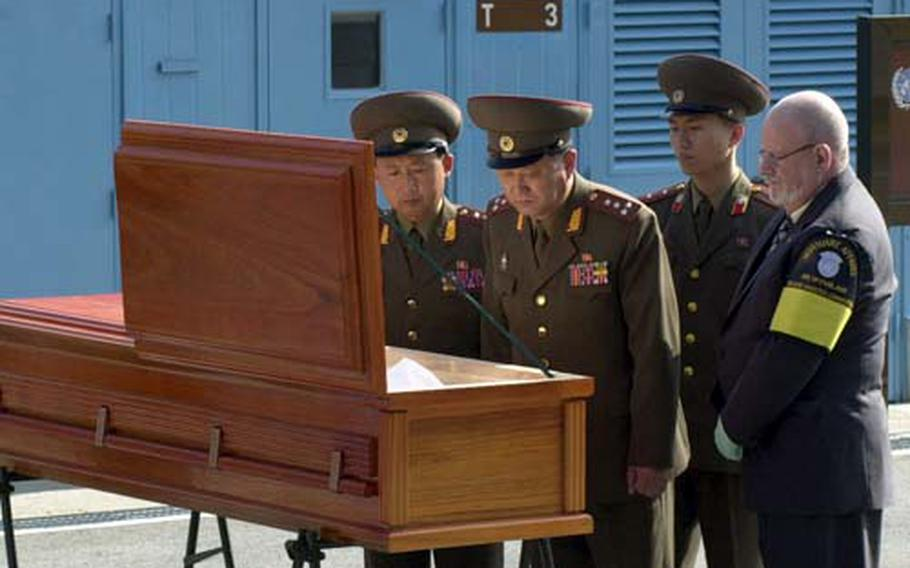North Korean military officers examine the remains of a soldier whose body was found south of the Military Demarcation Line in July after he apparently drowned. The United Nations Command Honor Guard subsequently handed the casket over the line to a group of North Korean soldiers during a repatriation ceremony Wednesday at the Demilitarized Zone.