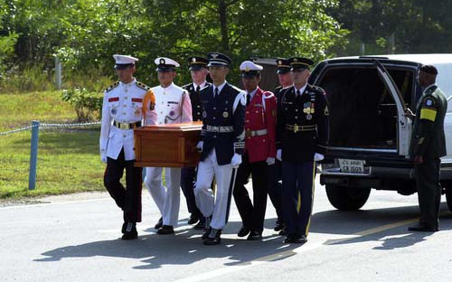 Members of the United Nations Command Honor Guard carry a casket bearing the remains of a North Korean soldier.