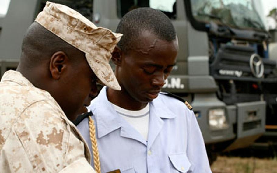 Capt. Serge Thierry Ella-Nguema of the Gabonese Light Aviation Military Branch, left, and Chief Warrant Officer Terence Whitlock of U.S. Marine Forces Africa review logistical guidelines during exercise Africa Endeavor 2009 in Gabon. The annual U.S. Africa Command-sponsored exercise tests the ability of different militaries to communicate with one another.