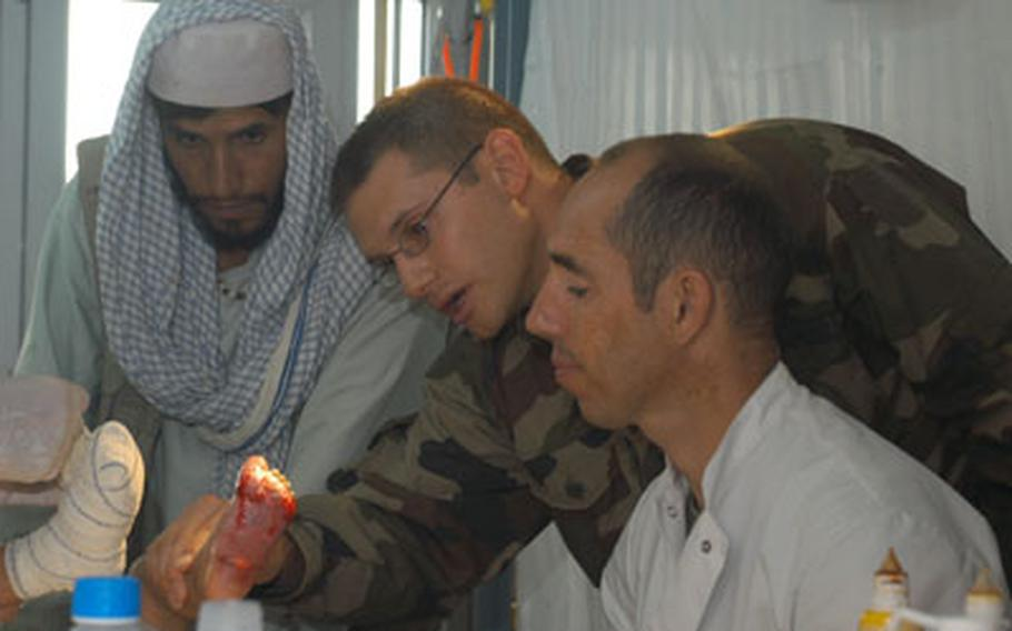 Maj. Julien, center, inspects Shahram's left foot. His father and Mickael, a French marine corporal and paramedic, look on.