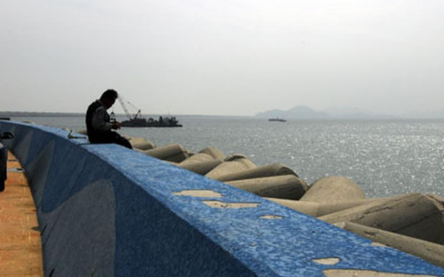 A man fishes off the Saemangum Seawall in Gunsan City, South Korea, on Sept. 28
