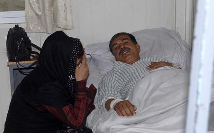 Arafa Sharpoor huddles at the hospital bedside of her husband, Ismail Mohammad Sharpoor, 45, who was wounded in a powerful bomb blast Thursday morning outside the Ministry of Interior and the Indian Embassy. Sharpoor was recovering at Jamhoriat Hospital, just up the road from the blast.
