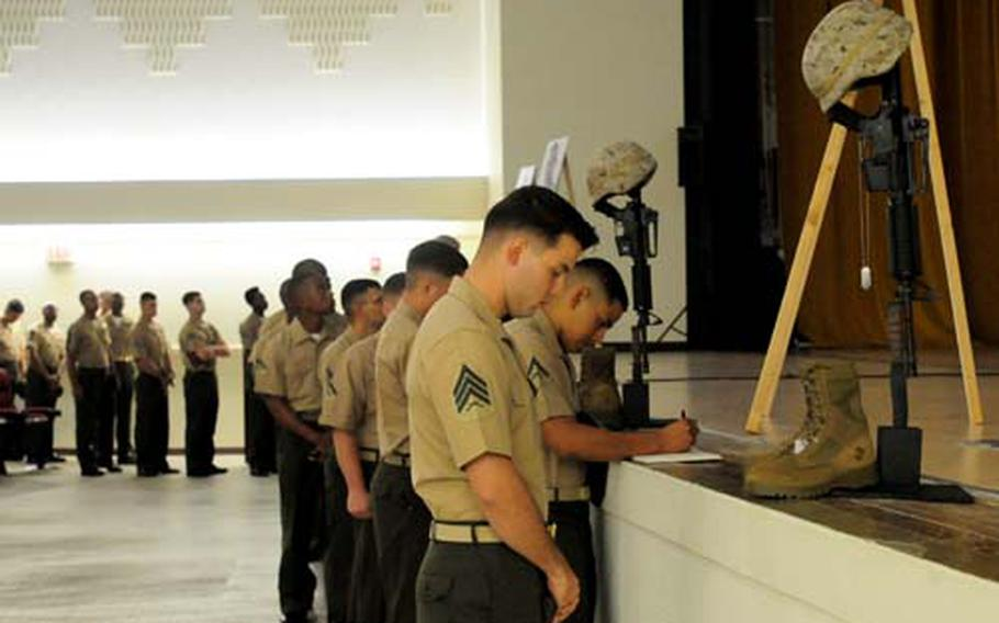 Friends and family members gathered at the Camp Hansen Base Theater on Okinawa Thursday to pay their respects to the three Marines and sailor that were killed Sept. 8 while part of an embed team that was training with the Combined Security Transition Command in the Sarkani District of Kunar province.