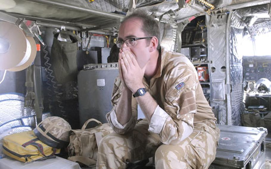 British Army Maj. Andy Haldane, 33, a member of the Medical Emergency Response Team, prepares himself mentally on the CH-47 Chinook helicopter after a call came through for a possible mission. The MERT can be ready in under 9 minutes from the time they get the call until take-off to pick up wounded soldiers or civilians.