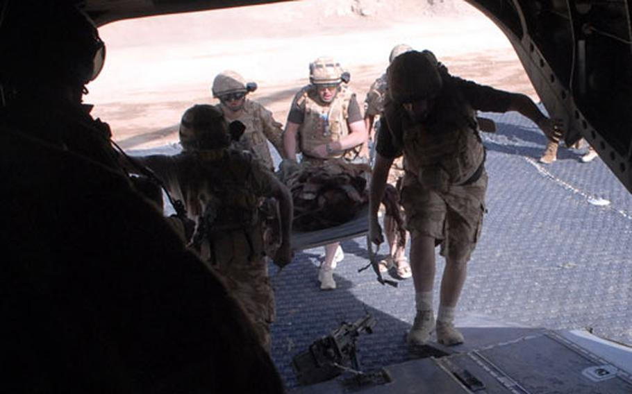 Members of the British military's Medical Emergency Response Team load a patient who was critically wounded by a makeshift bomb off the battlefield and onto their CH-47 Chinook helicopter where they can give him preliminary medical treatment.