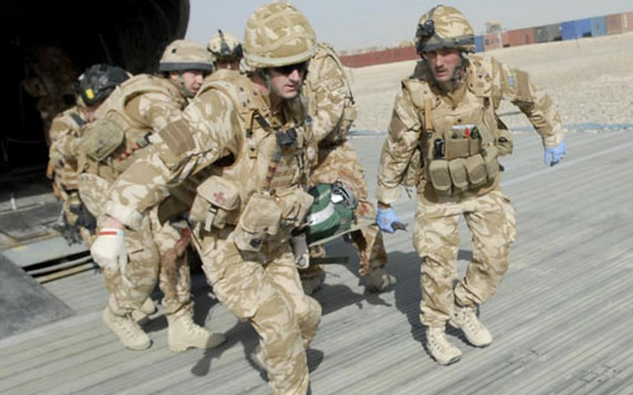 Members of the British military's Medical Emergency Response Team carry the critically wounded soldier from the CH-47 Chinook helicopter to an ambulance waiting on the ground near the hospital at Camp Bastion in Helmand Province.