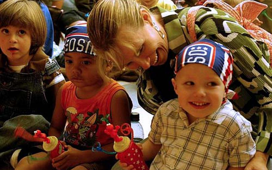 """Crew Woods, 3, is all smiles after his mother, Dayna, helped him don a USO bandana before the """"Sesame Street"""" show at Aviano Air Base, Italy. Mom was busy, also fitting Kai Christy, left, and watching over two other sons — Asher, 6, and Kabe, 8 — not pictured."""